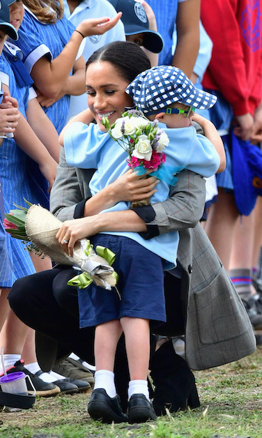 Here's Meghan showing off her maternal side as she interacts with some of her sweet little fans, who gave her the prettiest bouquets.