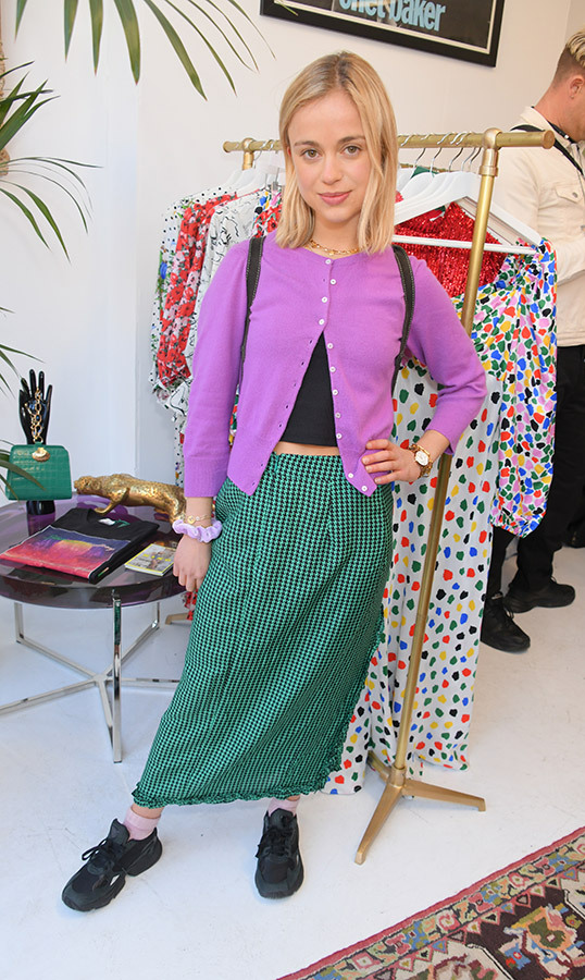 Lady Amelia Windsor looked totally 90s in a green gingham skirt, purple cardigan and black sneakers for the opening of the RIXO pop up shop on April 11.