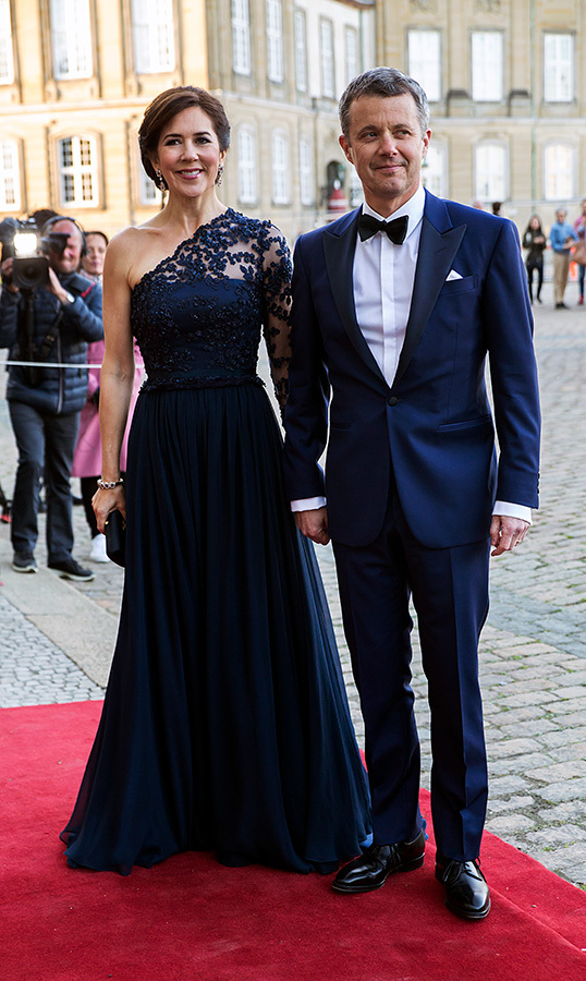 Crown Prince Frederik and Crown Princess Mary dusted off their finest evening wear for Princess Benedikte of Denmark's 75th birthday! The dapper duo arrived hand-in-hand for the party, hosted by Queen Margrethe of Denmark at Amalienborg Palace on April 29. Mary dazzled in navy blue lace one-shoulder gown, while her husband looked handsome as ever in a tuxedo.