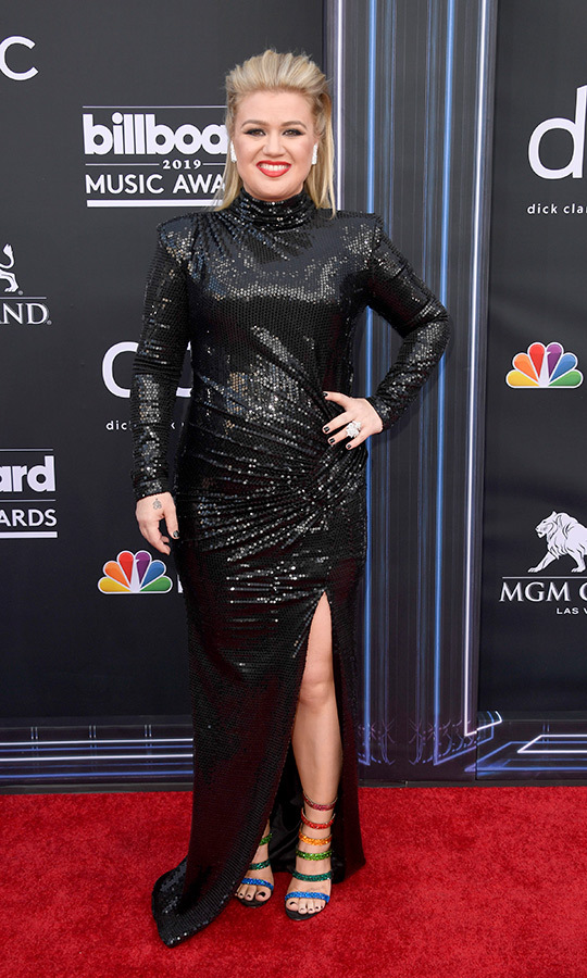 "<strong><a href=""https://ca.hellomagazine.com/tags/0/kelly-clarkson"">Kelly Clarkson</a></strong> wore a sleek black gown that was covered in sequins, which she paired with bright red lipstick and some awesome rainbow-striped footwear!