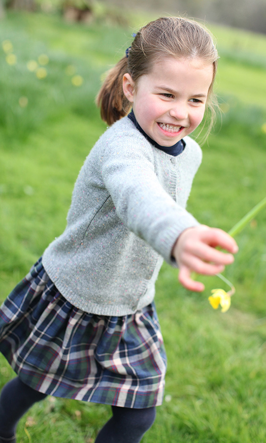In two other photos taken at the family's Anmer Hall home in Norfolk, Charlotte can be seen running on the grass, looking happy and enjoying her playtime.