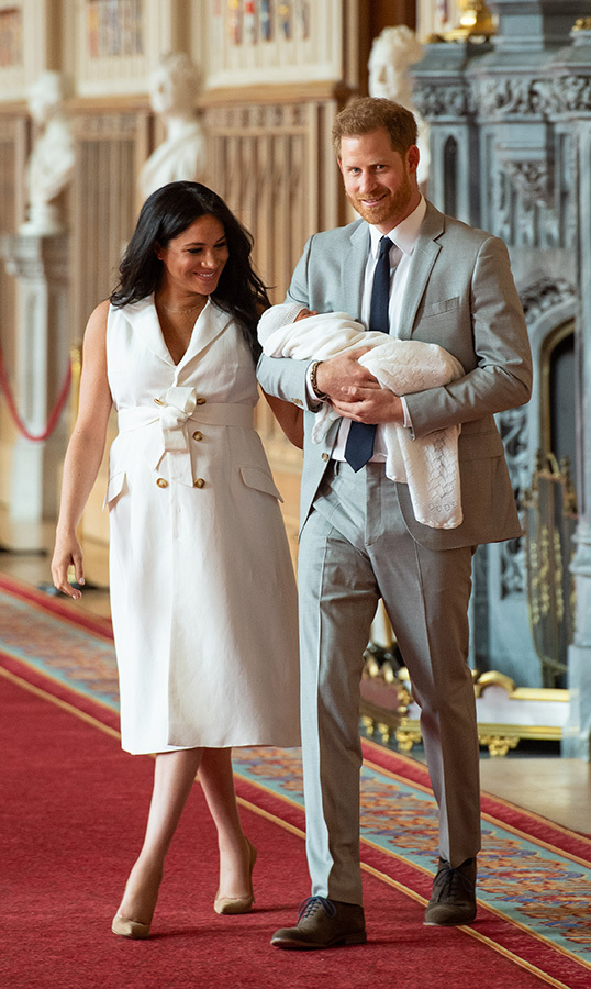 "The royal couple entered the room through a set of large doors, looking every inch the excited new parents. <a href-=""/tags/0/meghan-markle""><strong>Meghan</a></strong> dazzled in a white trench dress by British designer <strong>Grace Wales Bonner</strong> anchoring the look with <strong>Manolo Blahnik</strong> pumps.