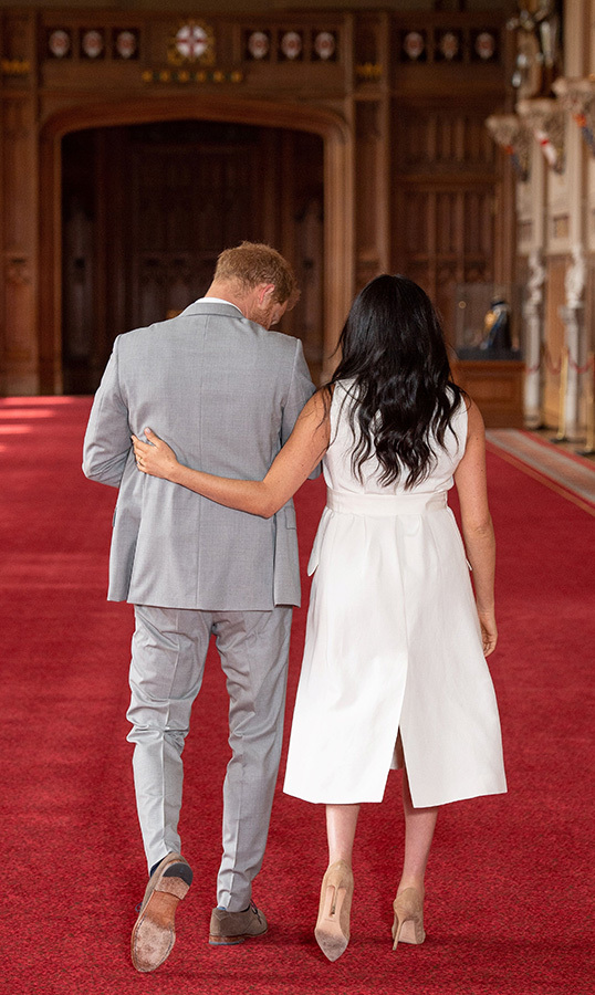 After the quick photo call, the new family of three was off. Meghan put a comforting arm around her husband's back.
