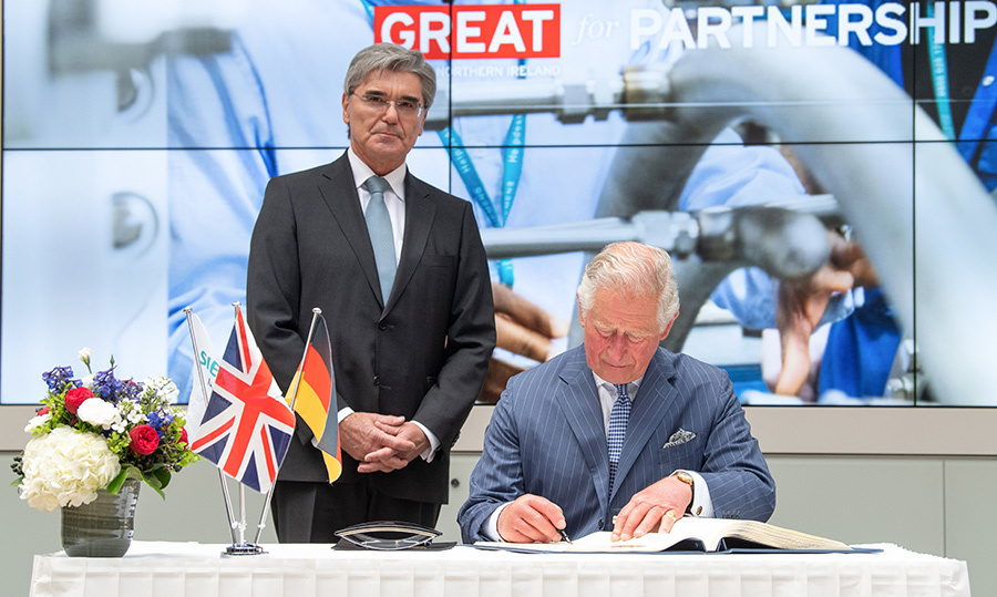 The Prince of Wales signed a guestbook next to CEO of Siemens Joe Kaeser during a visit at German engineering giant's headquarters.