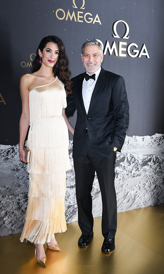 "Amal Clooney stepped out in a gorgeous fringe dress while at an OMEGA event celebrating the 50th anniversary of the moon landing in Orlando on May 9. The human rights lawyer was joined by husband <a href=""/tags/0/george-clooney""><strong>George Clooney</a></strong>, who wore a Giorgio Armani tuxedo. Amal's dress was also made by Armani, and she paired it with gold heels and a clutch. 
