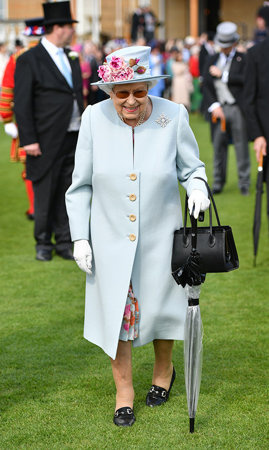 The Queen looked absolutely lovely in a powder blue coat with a floral dress underneath. Her coat perfectly matched the gorgeous hat, as she carried a black handbag and an umbrella.