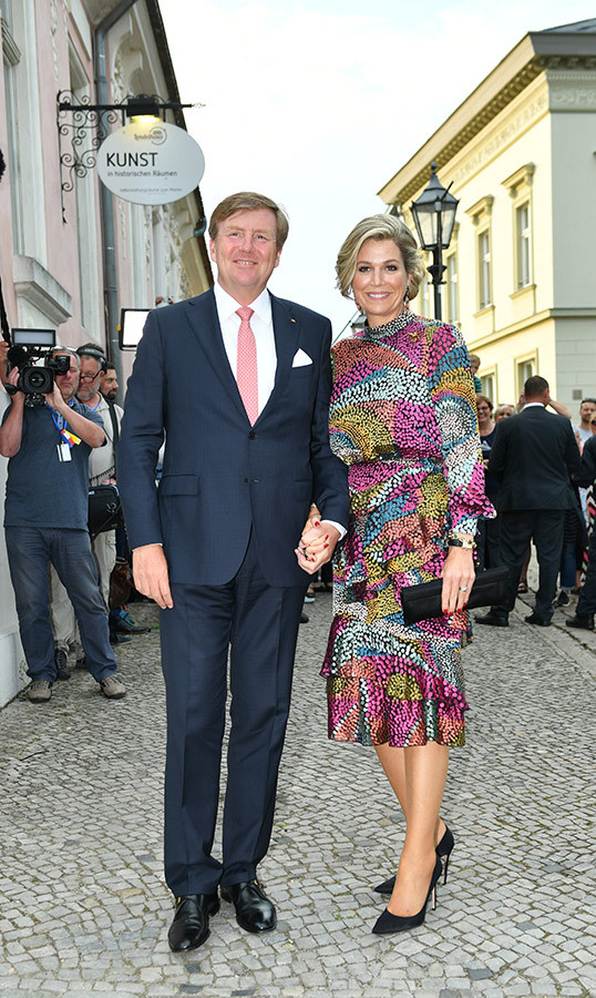 "King <a href=""/tags/0/willem-alexander""><strong>Willem-Alexander</a></strong> and <strong>Queen Máxima</strong> posed together while arriving to a dinner in the Historical Saftfabrik in Werder, Germany, on May 21. The queen dazzled in a colourful dress, paired with black pumps and a small clutch.
