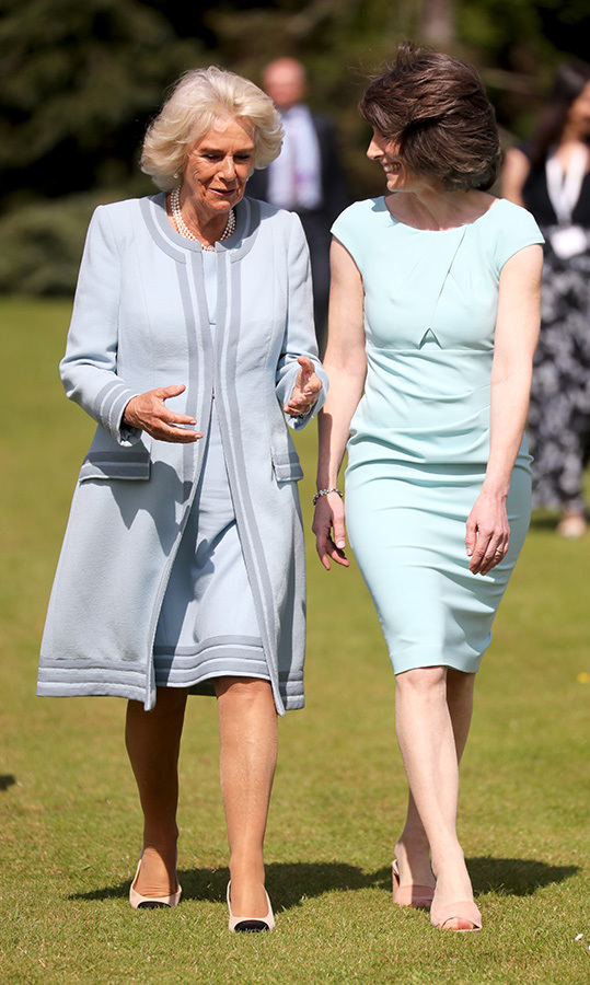 Camilla chatted with <b>Sarah Slazenger</b>, who runs the estate, while wandering the grounds before the reception. The duo matched in blue outfits.