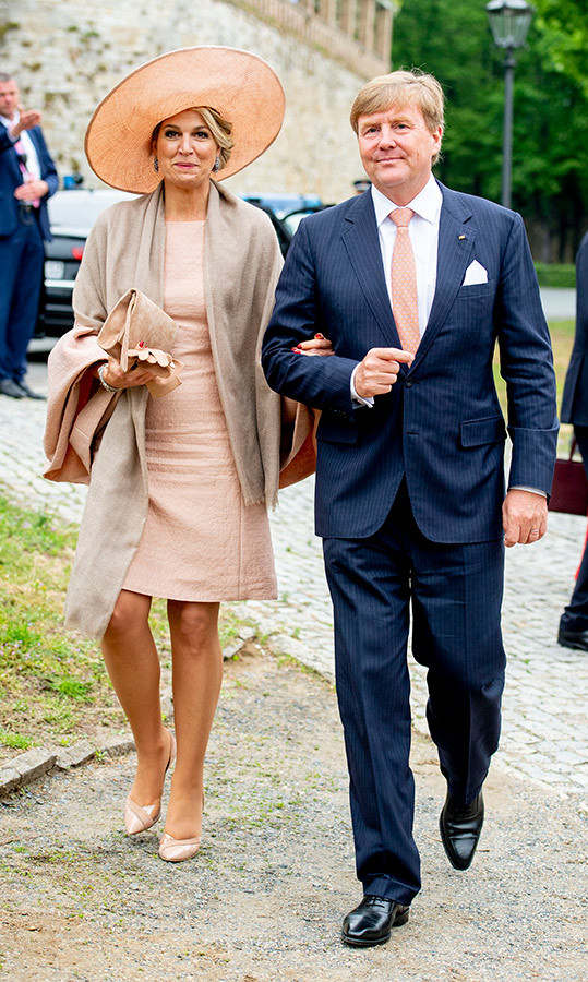 "Hats off to <a href=""/tags/0/queen-maxima""><strong>Queen Máxima</strong></a>! While in Germany with husband <a href=""/tags/0/king-willem-alexander""><strong>King Willem-Alexander</strong></a>, the royal dazzled in a peach dress and matching pumps. To keep warm on the windy day, the wrapped a beige shawl around her shoulders and topped the outfit off with a wide-brimmed hat.