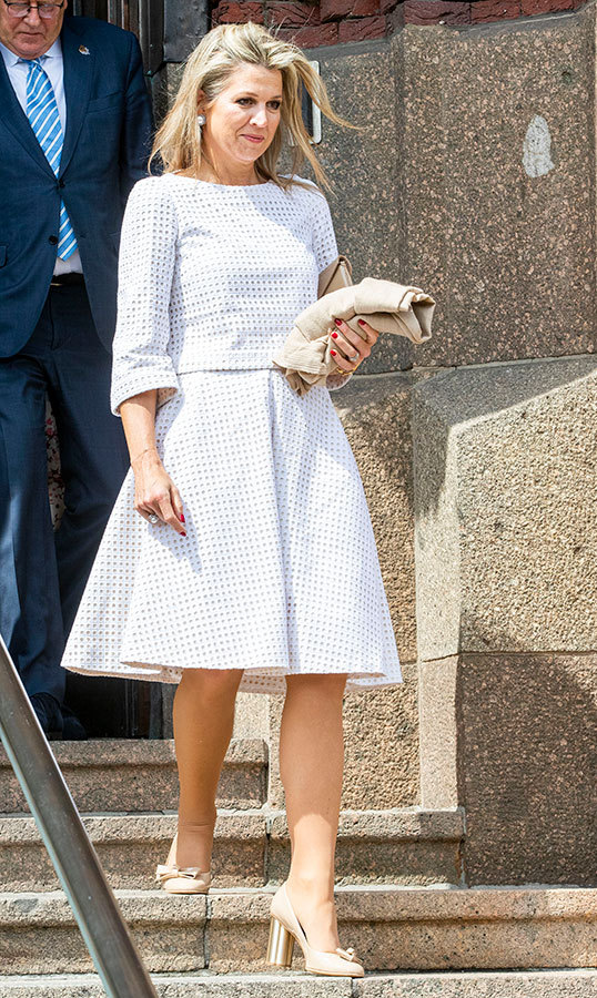 "<a href=""/tags/0/queen-maxima""><strong>Queen Máxima</strong></a> dazzled in a white checked dress, paired with block heels and a small clutch for a meeting in The Hague on May 28.