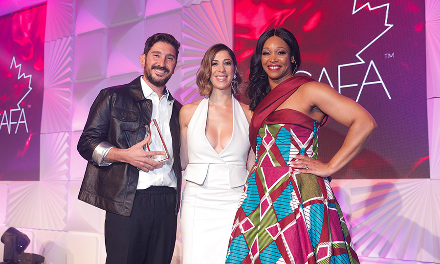 "<strong>Eran Elfassy</strong> and <strong>Elisa Dahan</strong> (left and centre) of <strong>Mackage</strong> were presented with the award for Outerwear Brand of the Year by <i>Cityline</i> host <strong><a href=""/tags/0/tracy-moore"">Tracy Moore</strong></a>.