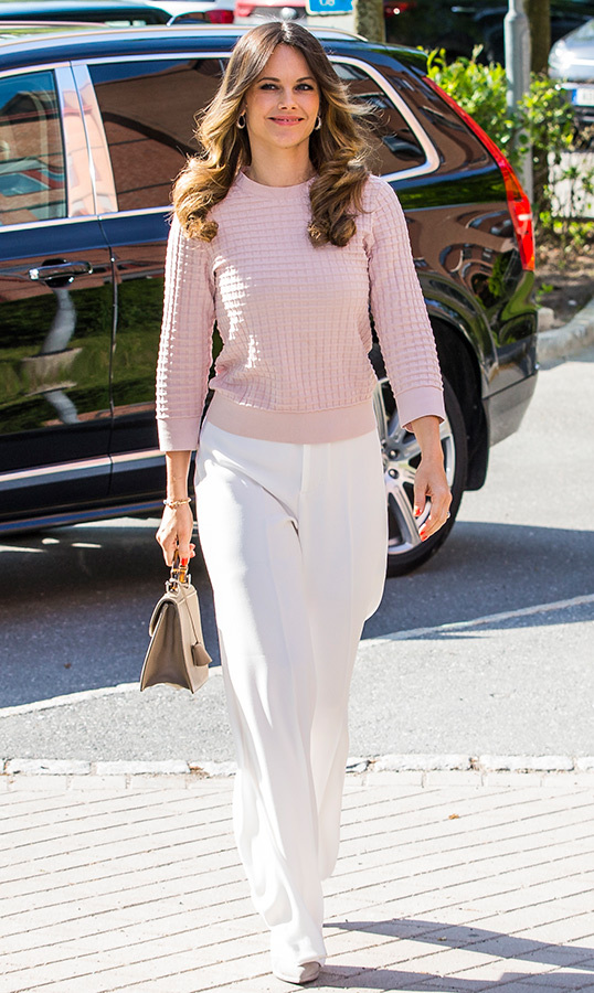 "<a href=""/tags/0/princess-sofia""><strong>Princess Sofia</strong></a> looked ready for summer in a blush pink sweater, white wide-legged trousers and a sweet beige handbag, fixed with a wooden handle. She fashioned her hair in bouncy curls, keeping her makeup simple with a pink lip and a subtle smoky eye. She was attending a symposium Recovery From Anorexia at Sophia Hemmet University on June 3 in Stockholm.