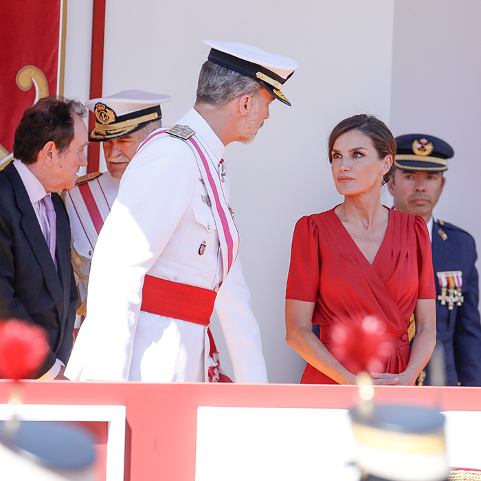 "<a href=""/tags/0/queen-letizia""><strong>Queen Letizia</strong></a> dazzled in a beautiful red v-neck dress while attending the Armed Forces Day on June 1 in Seville. She kept her hair up in a low bun.