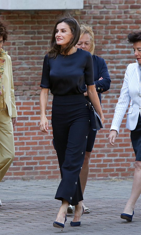 Queen Letizia of Spain was the picture of chic while visiting a traditional Students Residence on June 6. She paired high-waisted pants with a matching satin blouse, anchoring the look with navy blue pumps.