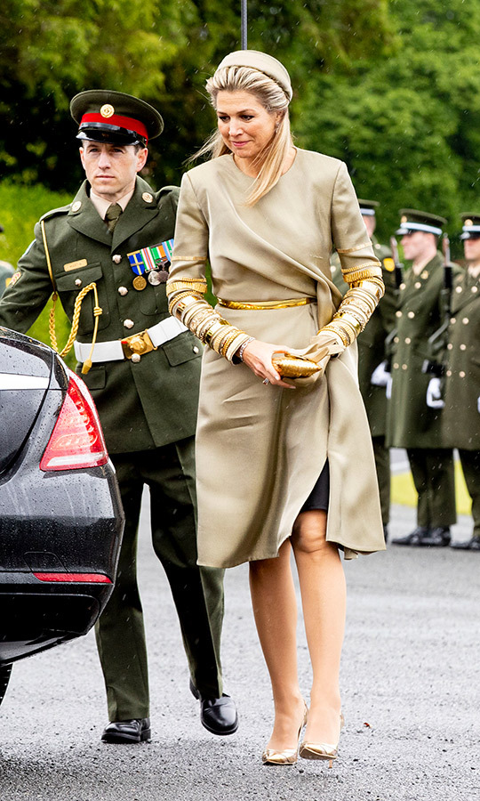 Queen Máxima looked chic in a beige wrap coat with gold accents, paired with metallic shoes and a taupe hat, on June 12 in Dublin.