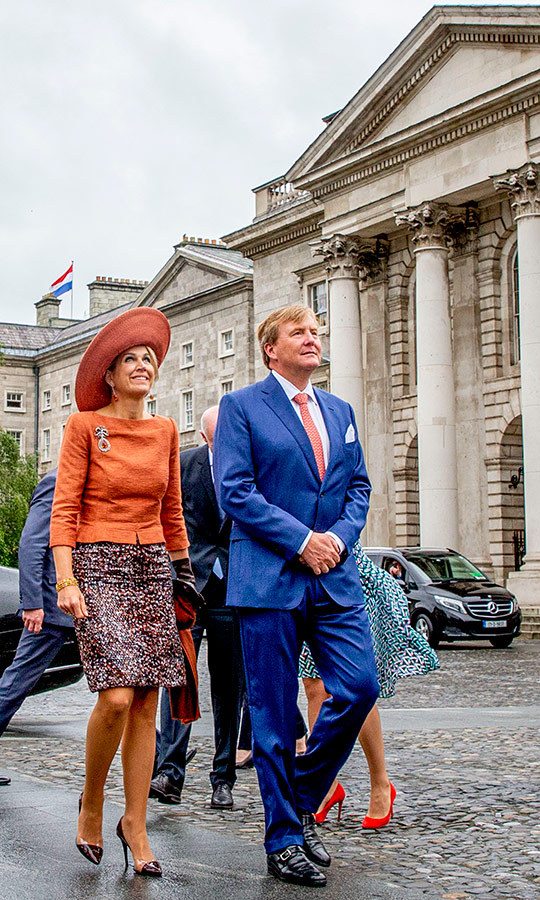 Hats off to Queen Maxima's latest outfit! During the couple's state visit to Ireland, the duo paid a visit to Trinity College on June 13. For the rainy day, the Argentina native dazzled in a rust orange top and matching wide-brimmed hat, paired with a speckled knee-length skirt and black pumps.