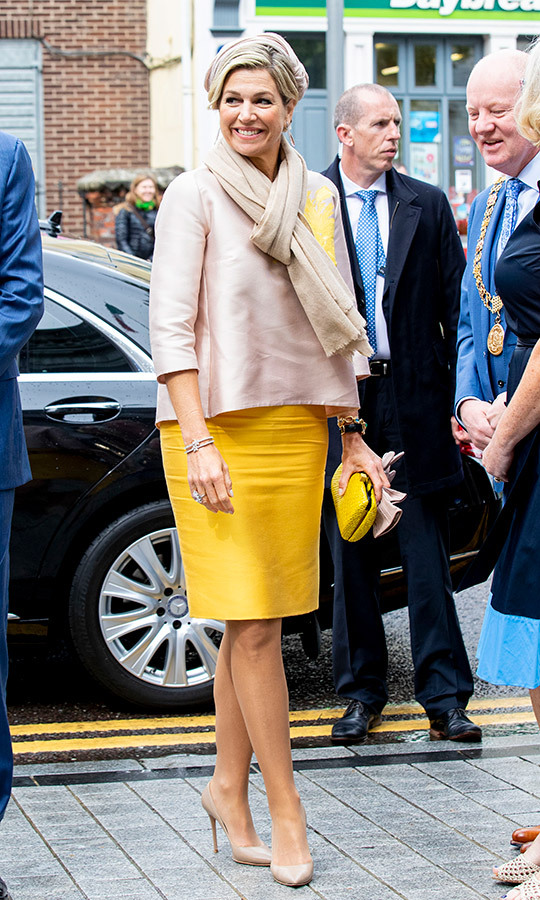 The Queen of The Netherlands brought some sunshine to a visit with the Lord Mayor in Cork on June 14. She paired a beige satin top with a bright yellow pencil skirt and matching clutch, keeping warm with a light scarf.