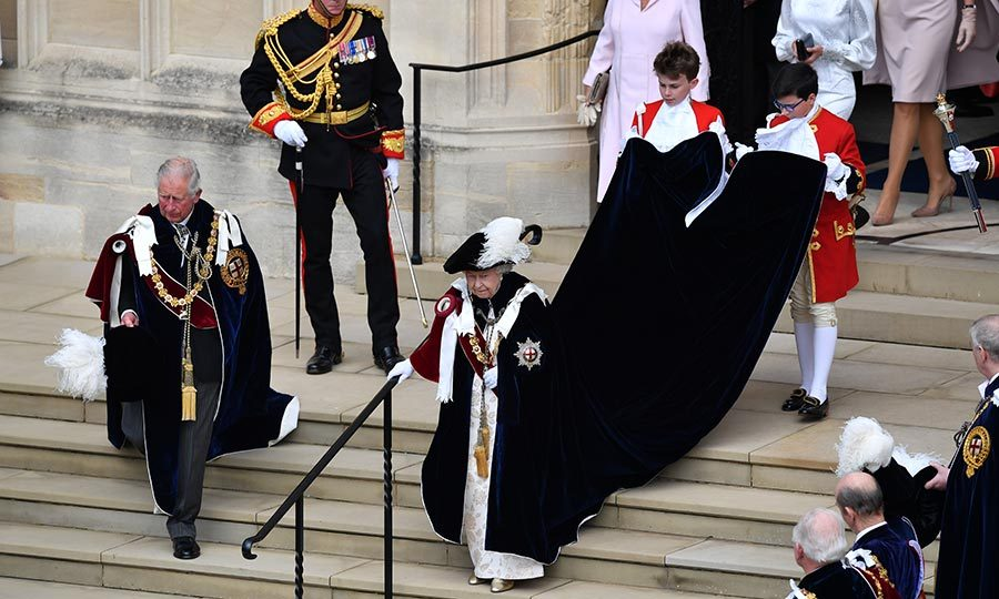 Look at that robe! Her Majesty needed assistance to keep her outfit off the stairs as she left the service.