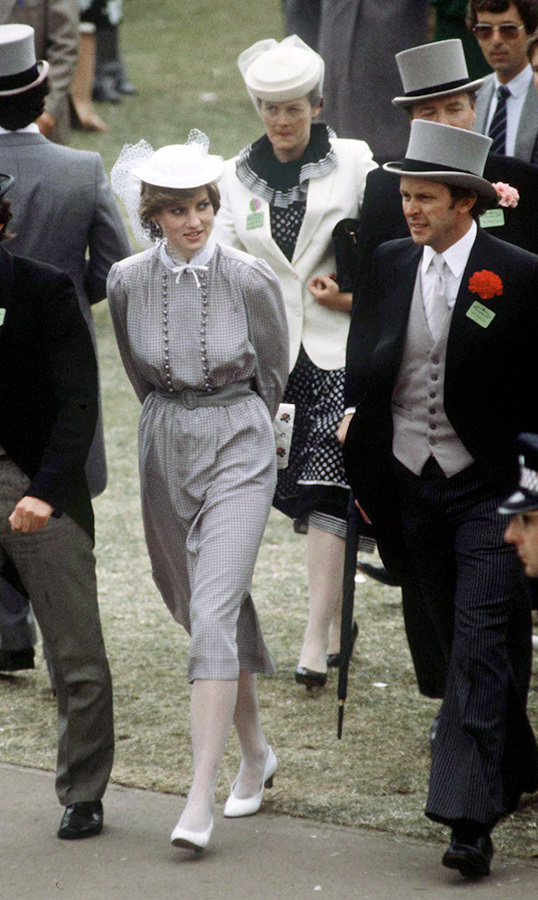 "The following day, Diana dazzled in a grey belted number, anchoring the look with white heels and topping it off with a white cap to match. Later to be known as the ""People's Princess,"" Diana was accompanied by her bodyguard <strong>Graham Smith</strong>, who looked handsome in a morning suit.