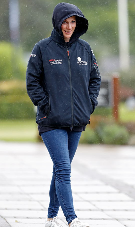 "<a href=""/tags/0/zara-tindall""><strong>Zara Tindall</a></strong> huddled in her raincoat to protect herself from a storm at the Celebrity Gold Classic in 2019.