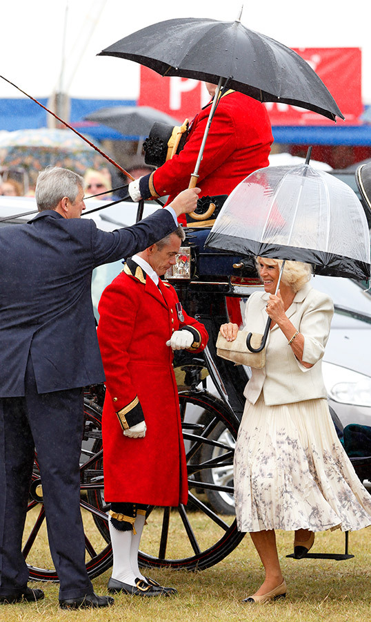 "Double duty! The <strong><a href=""/tags/0/duchess-of-cornwall"">Camilla, Duchess of Cornwall</a></strong> used not one, but two umbrellas at the Sandringham Flower Show in 2013.