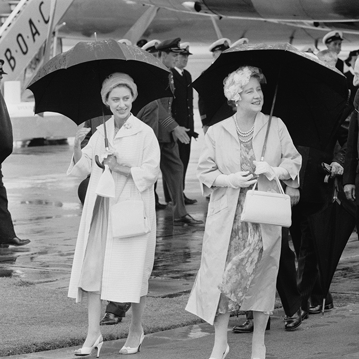 "The Queen Mother and <strong><a href=""/tags/0/princess-margaret"">Princess Margaret</a></strong> held umbrellas while arriving at London Airport in 1958.