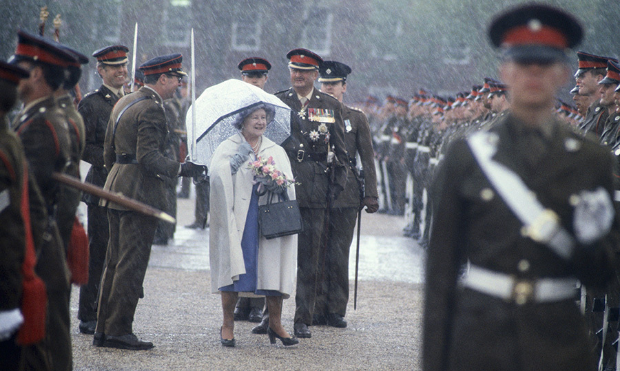 The <strong>Queen Mother</strong> was sheltered from a sudden downpour of rain while reviewing the guard of honour of the Royal Anglian Regiment in 1983.