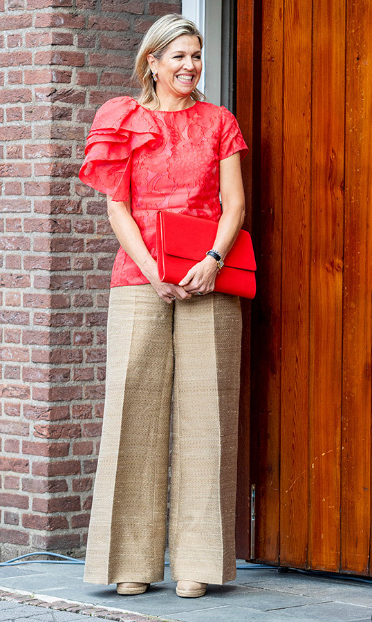 Queen Maxima visited the De Delerij Foundation for refugees on June 20, wearing a beautiful red blouse and beige wide-leg pants. She accessorized with an oversized red clutch to match!
