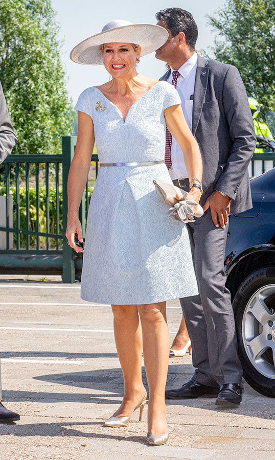 It's officially summer in the Netherlands, and Queen Máxima has the fashion savvy to prove it! During the opening of No Limits therapeutic horse stables on June 25, she wore a gorgeous powder blue tea dress, metallic heels and, of course, her trademark wide-brimmed hat.