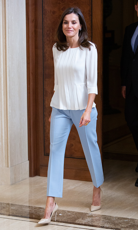 Queen Letizia paired powder blue trousers with a white pleated blouse and beige pumps for a day at Zarzuela Palace on June 27.