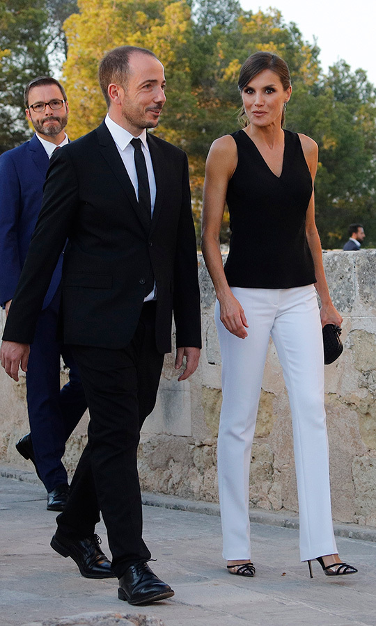 "<a href=""/tags/0/queen-letizia""><strong>Queen Letizia </strong></a> was a style star while attending the opening presentation of Atlantida Film Fest 2019 at Bellver Castle on July 2. For the occasion, she wore white straight-cut trousers with a black sleeveless camisole, anchoring the ensemble with her Manolo Blahnik 'Gotrianc' slingbacks and her Bottega Veneta 'Knot' clutch. As for accessories, she wore circle link earrings and a gold-plated Karen Hallam signature ring.