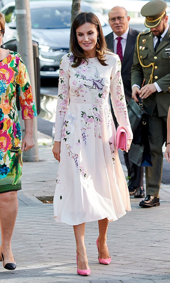 "<a href=""/tags/0/queen-letizia""><strong>Queen Letizia</strong></a> stunned in a cream floral-printed dress, making the outfit pop with bright pink suede pumps and a matching clutch for a meeting at the AECC (Spanish Association Against Cancer) on July 8.