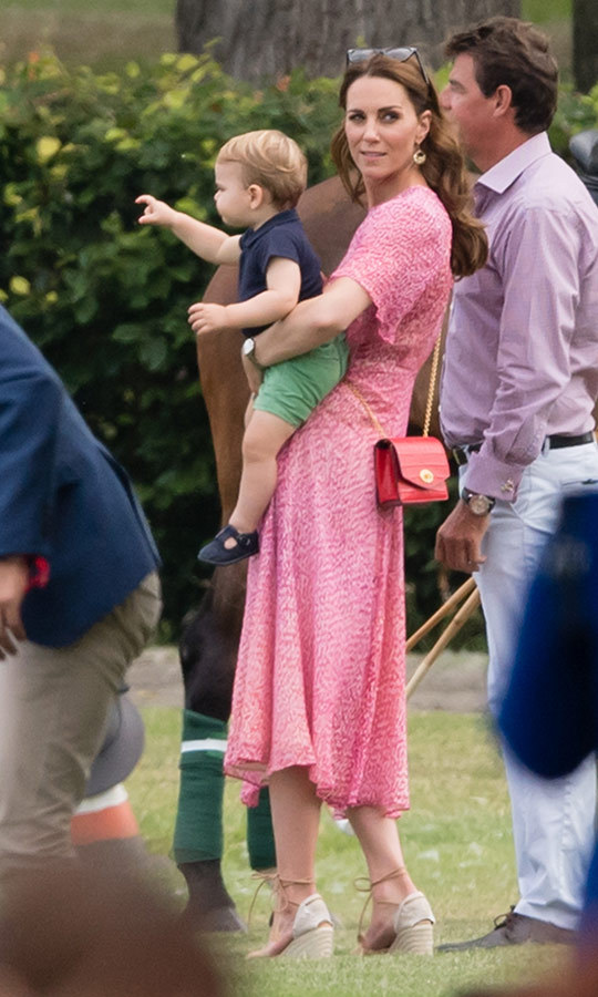 Kate looked happy and dressed perfectly for the warm, sunny summer weather in a pink dress with her Castañer espadrille wedges. She beamed as she held one-year-old son Louis in her arms, and at one point, he was seen toddling along just behind her. He looked completely adorable in green shorts and a blue polo shirt.