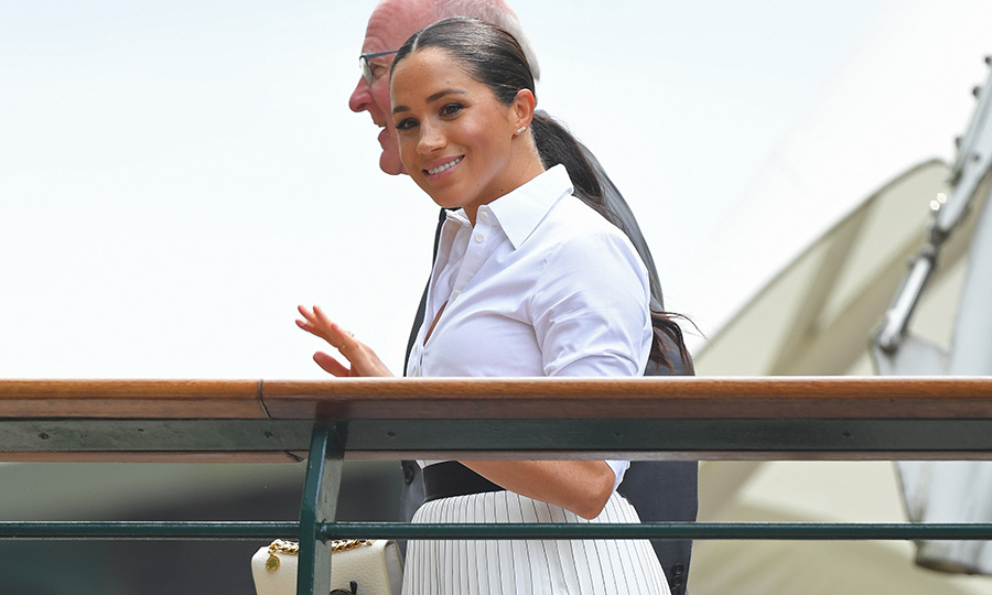 "<strong><a href=""/tags/0/meghan-markle"">Duchess Meghan</a></strong> looked happy and carefree as she arrived at Wimbledon wearing an outfit that looks fit for a tennis champ! She sported a white blouse, pleated cream skirt and black belt. 