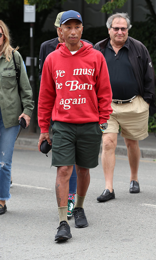 "<strong><a href=""/tags/0/pharrell-williams"">Pharrell Williams</a></strong> chose a casual look with a big message at Wimbledon on July 13. The rapper and pop star sported green shorts, black sneakers, a blue baseball cap and a red hoodie. 