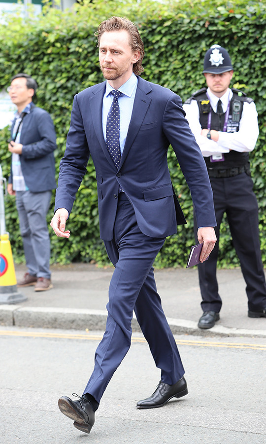 "<strong><a href=""/tags/0/tom-hiddleston"">Tom Hiddleston</a></strong> looked anything but low key (see what we did there?) when he arrived at Wimbledon on July 14. He looked utterly dashing in a blue suit, sky blue shirt, blue-and-white polka-dot tie and black shoes. 