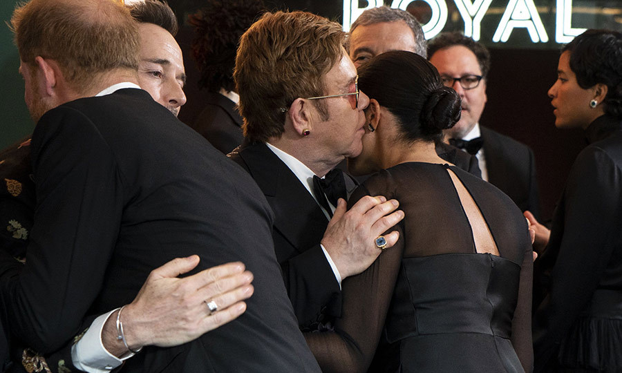 "Harry and Meghan also took some time to hug and say hello to <strong><a href=""/tags/0/elton-john"">Elton John</a></strong> and <strong><a href=""/tags/0/david-furnish"">David Furnish</a></strong> before the premiere. We wonder what Elton whispered in Meghan's ear?