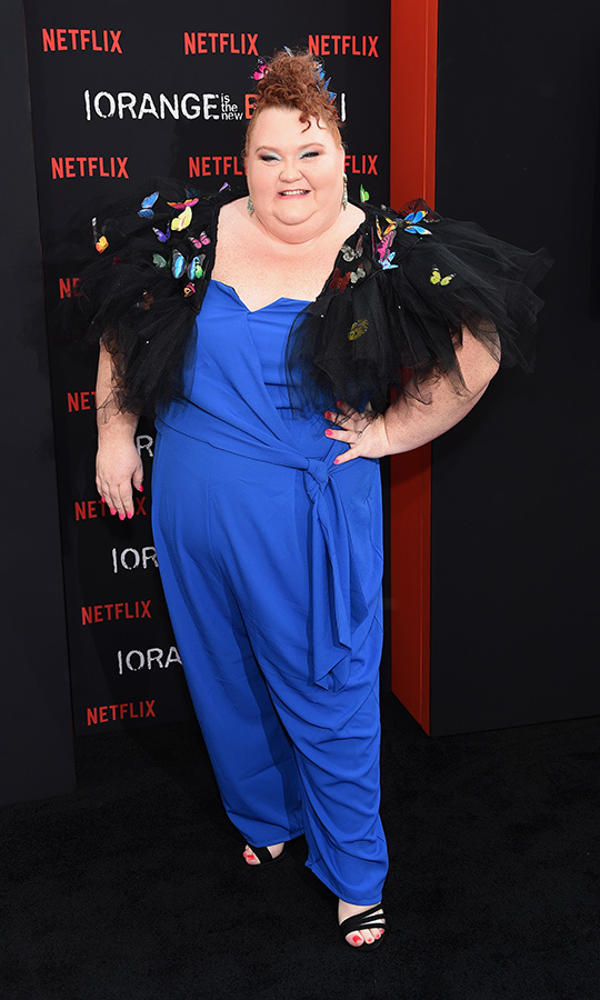 "<strong>Shawna Hamic</strong> (corrections officer Virginia ""Ginger"" Copeland) chose a blue jumpsuit, and opted for a black lace wrap peppered with rainbow coloured butterflies to cover her shoulders. She chose black strap sandals for her feet and sported red nail polish on her toes.