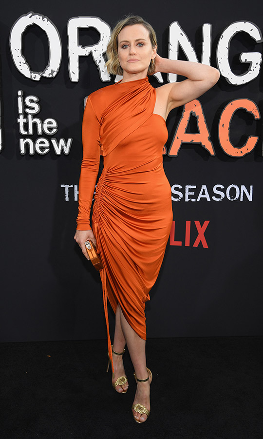 "<Strong><a href=""/tags/0/taylor-schilling"">Taylor Schilling</a></strong> took the show's name very literally with her outfit, which was an orange shoulderless dress with a top wrap that only covered one arm and shoulder. 