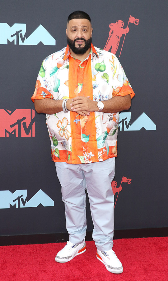 "<strong><a href=""/tags/0/dj-khaled"">DJ Khaled</a></strong> was true to his personal sense of casual style, rocking an orange and white Hawaiian shirt with grey pants and white shoes.