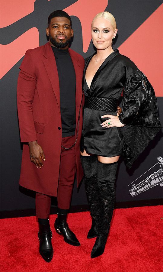 Newly engaged couple <strong>PK Subban</strong> and <Strong>Lindsey Vonn</strong> looked stunning together! PK chose a knee-length red jacket with matching pants, a black turtleneck and some seriously stylish shoes. Lindsey looked gorgeous in all black.