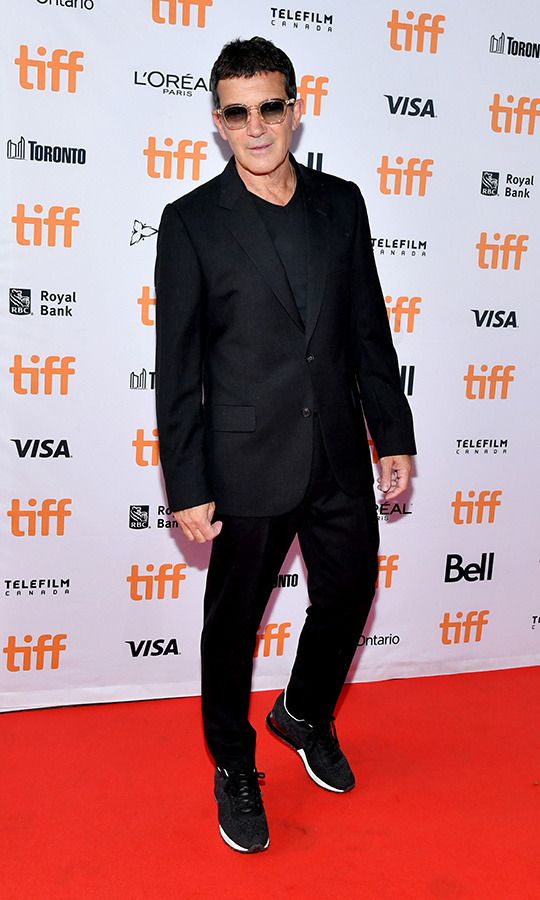 "Caliente! <strong><a href=""/tags/0/antonio-banderas"">Antonio Banderas</a></strong> looked cool on the red carpet for the Canadian premiere of <i>Pain and Glory</i> at <Strong><a href=""/tags/0/tiff"">TIFF</a></strong> 2019. He wore black suit, black pants, black shirt, running shoes and shades. 