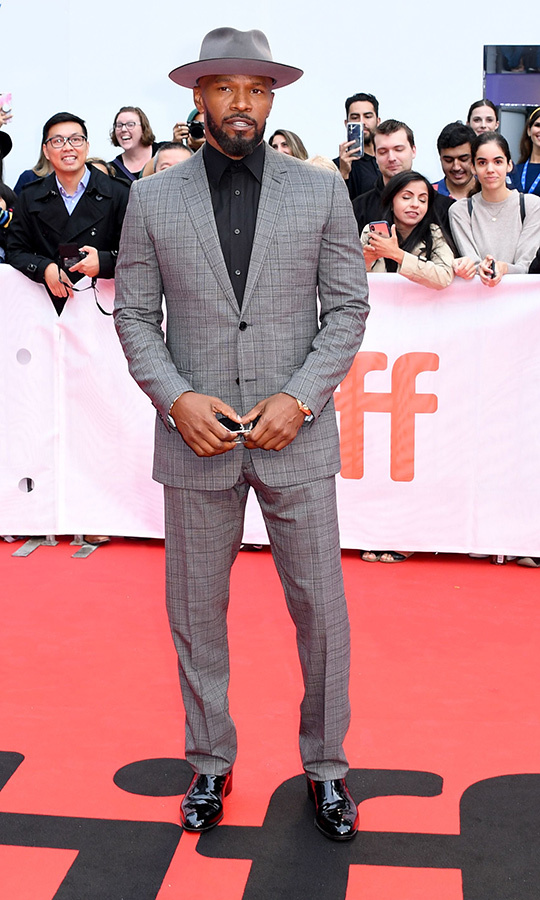 "<strong><a href=""/tags/0/jamie-foxx"">Jamie Foxx</a></strong> looked his usual dapper self with a grey suit, black shirt and matching grey hat on the <i>Just Mercy</i> red carpet.