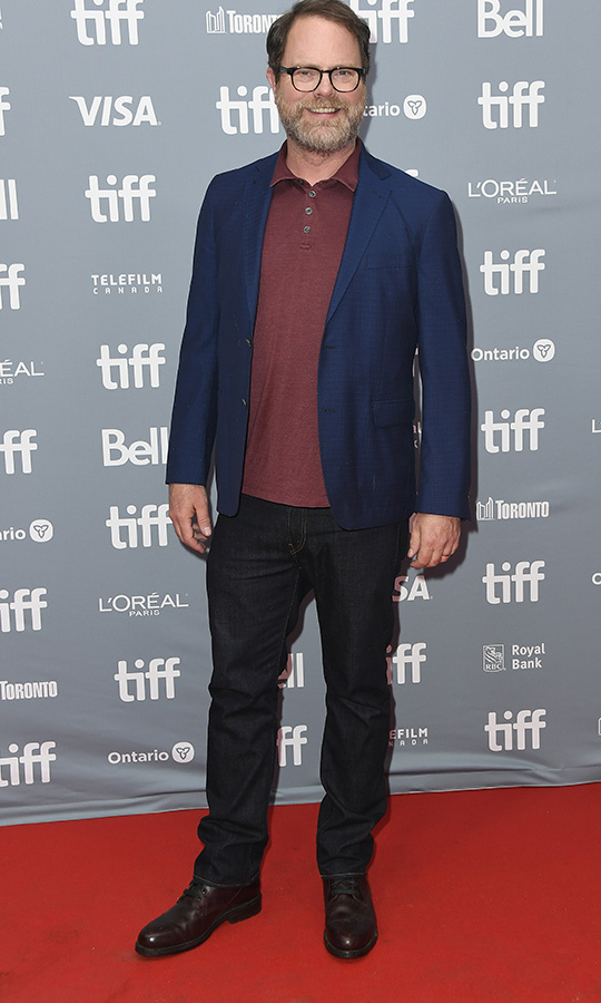 "<strong><a href=""/tags/0/rainn-wilson"">Rainn Wilson</a></strong> showed up to the press conference in a blue jacket, burgundy polo shirt black pants and black kicks.