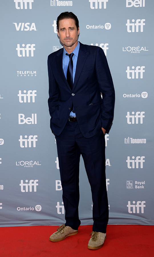 "<strong><a href=""/tags/0/luke-wilson"">Luke WIlson</a></strong> chose a slick blue suit with brown running shoes for the <i>Goldfinch</i> press conference.