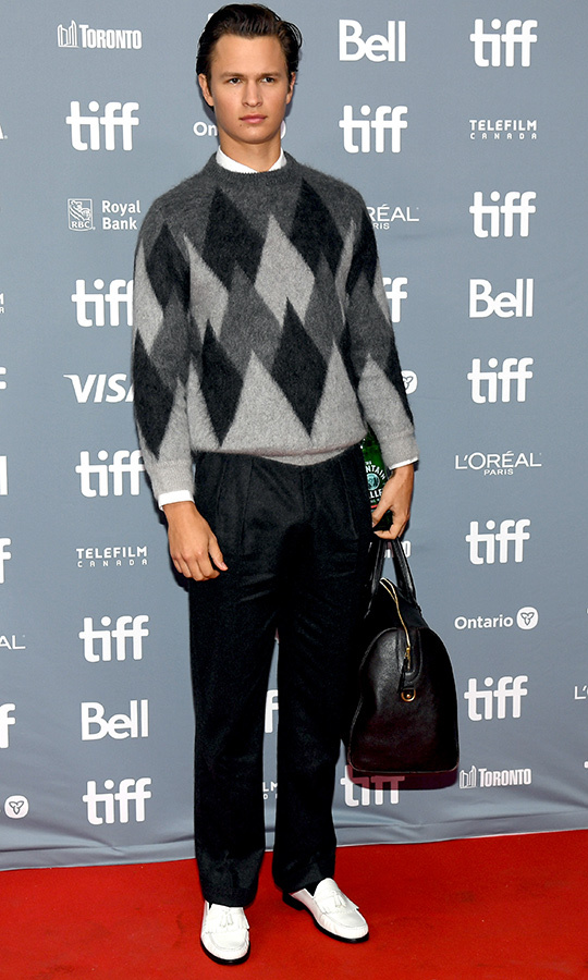 "<strong><a href=""/tags/0/ansel-elgort"">Ansel Elgort</a></strong> looked ready for prep school in an Argyle sweater, dress pants and white shoes with a bowling bag at the <i>Goldfinch</i> press conference. 