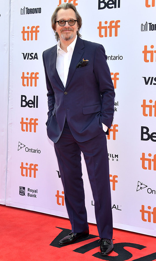 "<strong><a href=""/tags/0/gary-oldman"">Gary Oldman</a></strong>'s suit on the red carpet of <I>The Laundromat</i> is almost a Joker reference! It's a blue that's almost purple and we wonder if he's excited for the <i>Joker</i> red carpet on Sept. 10!