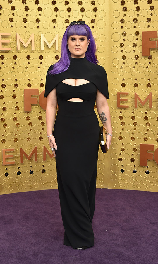 "<strong><a href=""/tags/0/kelly-osbourne"">Kelly Osbourne</a></strong> was rocking a look that perfectly married Hollywood glam with punk! She sported a black caped dress with cutouts and purple hair. She accessorized with a gold clutch and a black hairband complete with a bow. 