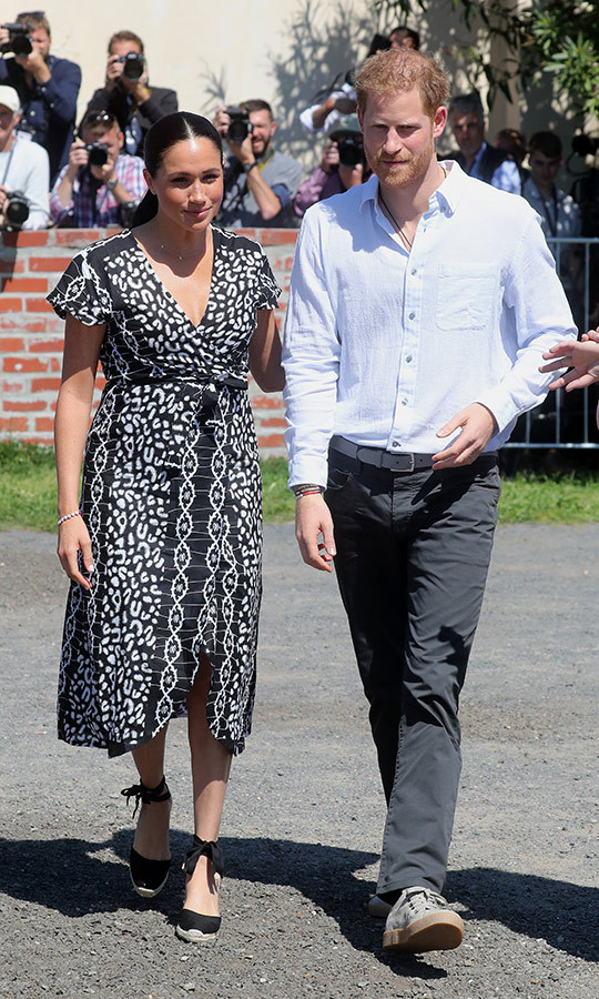 Meghan looked absolutely stunning in a black dress with white leopard print patterns and black espadrilles. Harry looked relaxed in grey pants and a simple shirt.