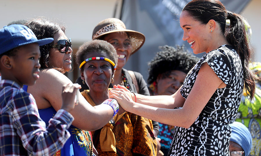 Meghan joyfully greeted those who had arrived outside the centre in Nyanga township, smiling and laughing as she held their hands.